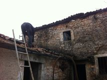Man working on the roof. Man repairing old roof, of the stone house Stock Photography