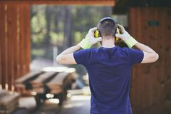 Man working in sawmill. Rear view of the worker with headset Stock Photos