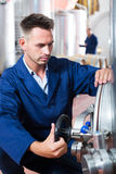Man working on secondary fermentation equipment Stock Photography