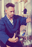 Man working on secondary fermentation equipment Royalty Free Stock Photos