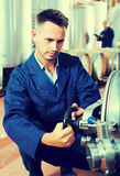 Man working on secondary fermentation equipment Stock Image