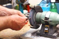 Man working with sharpening machine tool. Detail of hands working on sharpening machine tool stock image