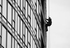 Man Working on Skyscraper. Man suspended while working on side of skyscraper building Stock Images