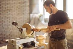 Man working at small wood lathe, an artisan carves piece of wood. Carpenter man working at small wood lathe, an artisan carves piece of wood using manual lathe Royalty Free Stock Photo