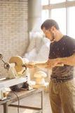 Man working at small wood lathe, an artisan carves piece of wood. Carpenter man working at small wood lathe, an artisan carves piece of wood using manual lathe Royalty Free Stock Image
