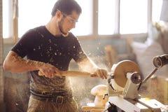 Man working at small wood lathe, an artisan carves piece of wood. Carpenter man working at small wood lathe, an artisan carves piece of wood using manual lathe Stock Photos