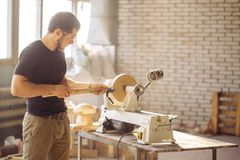 Man working at small wood lathe, an artisan carves piece of wood. Young carpenter processing wooden plank on special woodworking machine Royalty Free Stock Photos