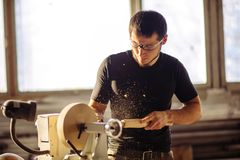 Man working at small wood lathe, an artisan carves piece of wood. Young carpenter processing wooden plank on special woodworking machine Royalty Free Stock Photography