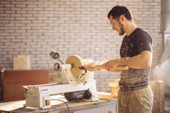 Man working at small wood lathe, an artisan carves piece of wood. Young carpenter processing wooden plank on special woodworking machine Stock Photography