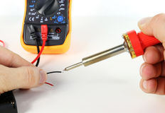 Man working with soldering iron and electronic measuring device Royalty Free Stock Photography