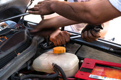 Man working with spanner on car. Workers with tools repairing car stock image