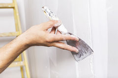 Man working with spatula. Renovating home interior Stock Photos
