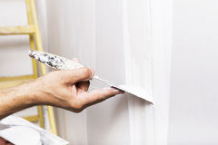 Man working with spatula. Renovating home interior. Man working with spatula. Ladder in the background stock image
