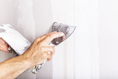 Man working with spatula. Renovating home interior. Man working with spatula. Patterns Royalty Free Stock Photography