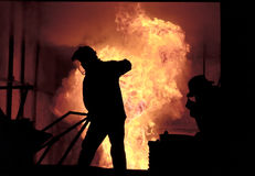 Man is working in the splashing molten iron - Stock Image Stock Images