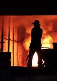 Man is working in the splashing molten iron - Stock Image Stock Photos