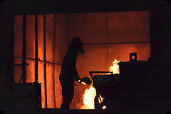 Man is working in the splashing molten iron - Stock Image Royalty Free Stock Photography