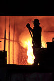 Man is working in the splashing molten iron - Stock Image Royalty Free Stock Images