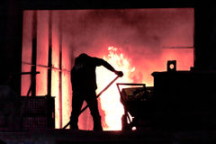 Man is working in the splashing molten iron - Stock Image Stock Photography