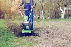 Man working in the spring garden with tiller machine.  royalty free stock images
