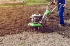 Man working in the spring garden with tiller machine.  royalty free stock photo