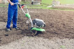 Man working in the spring garden with tiller machine.  royalty free stock photography