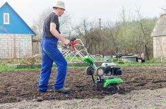 Man working in the spring garden with tiller machine.  royalty free stock image