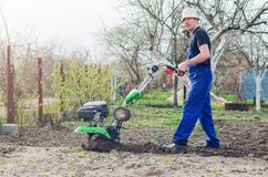 Man working in the spring garden with tiller machine.  stock photography