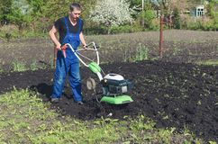 Man working in the spring garden with tiller machine.  stock photos