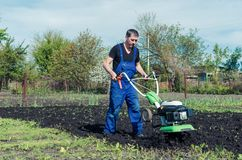 Man working in the spring garden with tiller machine.  stock images