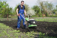 Man working in the spring garden with tiller machine.  royalty free stock photos