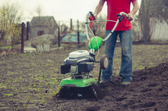 Man working in the spring garden with tiller machine Royalty Free Stock Photos