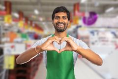 Man working at supermarket making heart gesture with hands. Indian male smiling as working at supermarket or hypermarket and wearing green apron making heart royalty free stock image