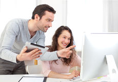 Man working on tablet with his co-worker stock images