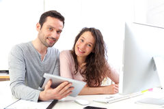 Man working on tablet with his co-worker Royalty Free Stock Image