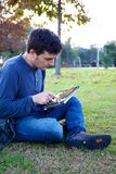 Man working with tablet in park. Happy young man reading tablet ipad in park in winter Stock Photography