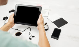 Man working on tablet pc. With blank screen, notepad and smart phone on white table royalty free stock image