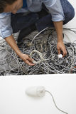 Man Working On Tangled Computer Wires Royalty Free Stock Photo