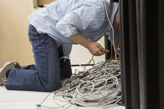 Man Working On Tangled Computer Wires Royalty Free Stock Photos
