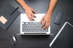 A man is working by using a laptop computer on vintage wooden ta royalty free stock image