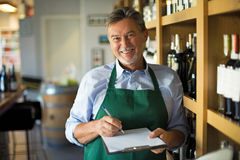 Man working in wine shop. Mature man working in wine shop stock photo