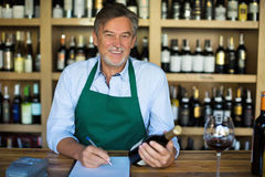 Man working in wine shop. Mature man working in wine shop royalty free stock image