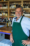 Man working in wine shop. Mature man working in wine shop royalty free stock photography