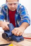 Man working wood with electric planer Stock Images
