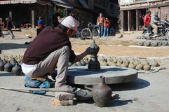 Man is working on a wood potter's wheel,Nepal Stock Image