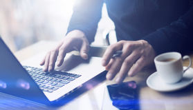 Man working at the wooden table at modern loft office.Man sitting at workplace and typing on laptop keyboard.Blurred. Background.Horizontal,visual effects stock photography
