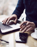 Man working at the wooden table at modern loft office.Man sitting at workplace and typing on laptop keyboard.Blurred Stock Photos