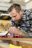 Man working at workshop with musical instruments Royalty Free Stock Photo
