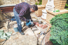 Man working in yard puncher Stock Photo