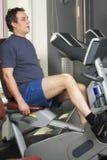 Man at workout on bicycle machine Royalty Free Stock Photos